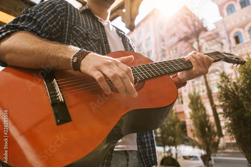 Music everywhere. Close up of male hands holding chord and touching strings
