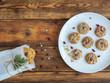 Selbstgemachte Weihnachts Cranberry Kekse mit Zuckerguss verziert auf einem weißen Teller und eine Papiertüte mit Keksen