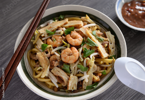 A bowl of shrimp noodle garnished with egg omelette and bean sprouts. - 228286791