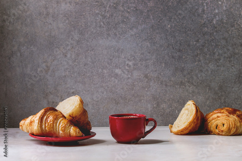 Wall mural Fresh baked whole and sliced croissant with red cup of coffee espresso on white marble table with grey wall at background. Caffe breakfast