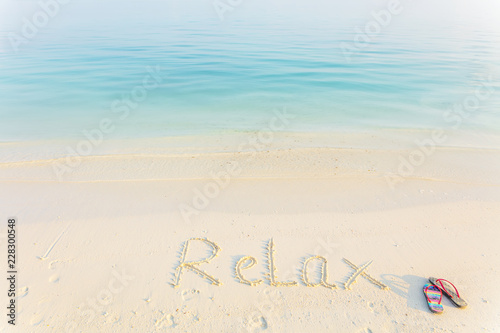 Sticker The Word Relax Written in the Sand on a Beach with flup flops at morning sea background