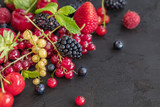 Mixed berries on a dark background with selected focus. Strawberries, Raspberries Blackberries, cherries, red and yellow currents. Healthy Living and Nutritious Food concept.