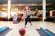 Leinwandbild Motiv Focused happy woman enjoying bowling