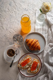 Continental breakfast captured from above (top view, flat lay). Coffee, orange juice, croissant, sandwich and flowers. Copy space. - 228311576