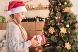 side view of adorable preteen kid in santa hat standing with present near christmas tree at home