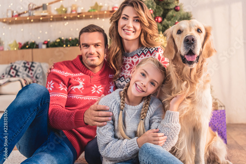 Leinwanddruck Bild smiling family with golden retriever dog sitting near christmas tree with gifts