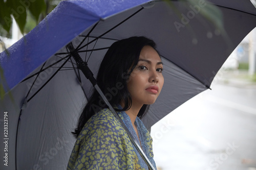 Sticker Side view of beautiful Filipino female with umbrella looking away while standing on street on rainy day