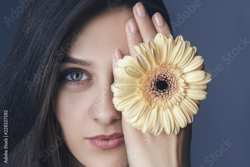 Foto Murales Close up portrait young beautiful woman with yellow flower