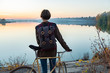 Female cyclist enjoying beautiful blue hour scene by the lake. Woman stands with bike and looks at beautiful lake and sunset