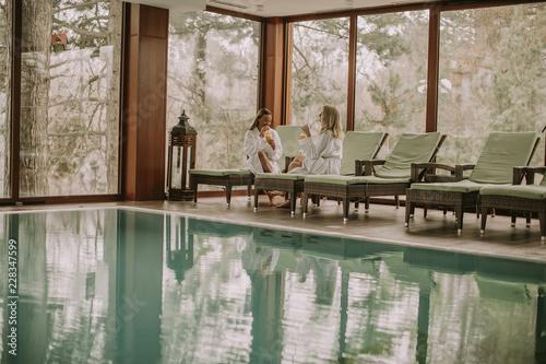 Leinwandbild Motiv Pretty young women relaxing on the deckchair by the swimming pool