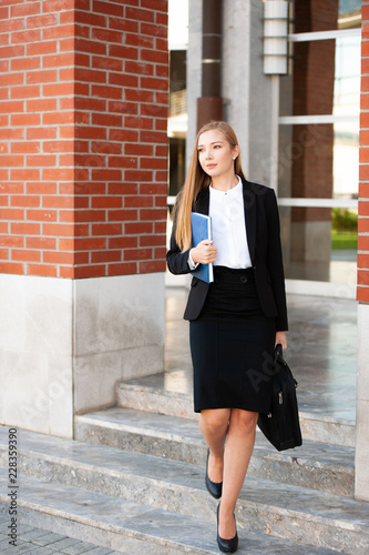 Business woman walking on stairs outdor carying business folder and hand bag