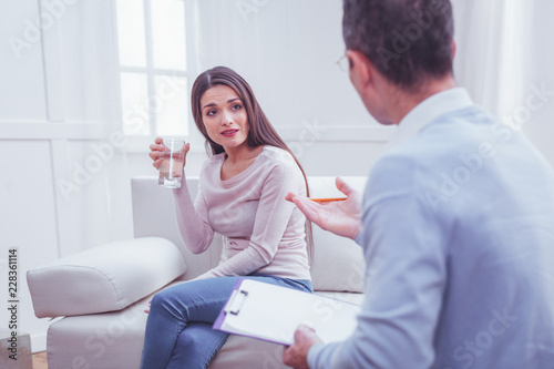 Leinwandbild Motiv Hope in eyes. Young charming long haired woman holding a glass of water and looking at her personal psychologist expressing surprise on her face while sitting on sofa