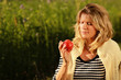 Happy mature woman regarding an apple in the grass outdoor