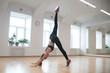 Slender beautiful girl is engaged in sports, performs stretching exercises in the gym.