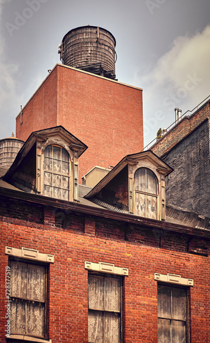 Vintage toned picture of water tank on roof of an old building, New York City, USA. - 228377519