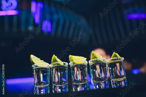 Silver tequila shots with ice and lime on black table background. - 228378148