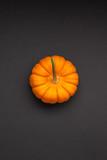 Small orange pumpkin black color paper background - 228384385