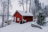 Red house at the lakeside in Finland. - 228390184