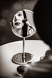 portrait of the beautiful young woman doing her make-up and looking in the mirror