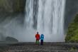 Couple looking at powerfull waterfall Skogafoss