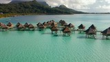 Aerial wide shot of overwater bungalows in a turquoise lagoon with Mountains in the background, Bora Bora, French Polynesia - 228416577