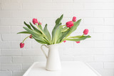 Red tulips with green leaves in white jug on table against painted brick wall - 228421321