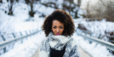 Stylish afro hair woman winter portrait. Female wearing warm wool scarf. © Dirima