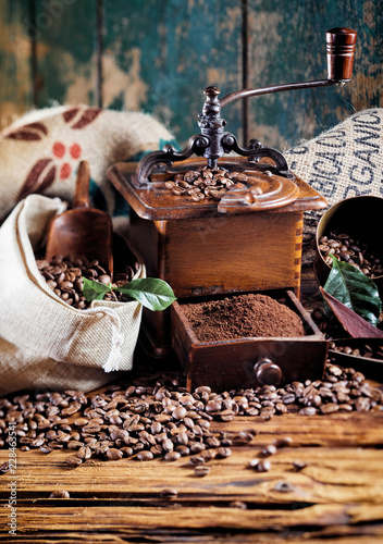 Wall mural Retro wooden coffee mill with roasted beans