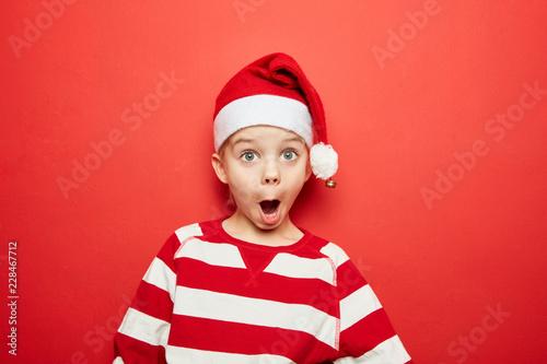 Leinwandbild Motiv Überraschtes Kind beim Staunen zu Weihnachten