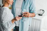 cropped image of young couple clinking with wineglasses in kitchen - 228468798