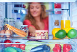 Woman taking gateau form fridge full of groceries. Unhealthy eating concept. Picture taken from the inside of fridge. - 228472339
