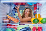 Woman taking food from fridge full of groceries. Picture taken from the inside of fridge. - 228472530