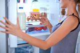 Woman breaking diet by taking cheesecake from fridge. Fridge full of groceries. - 228473957