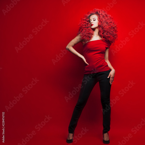 Leinwanddruck Bild Portrait of beautiful young woman with red hair on red background