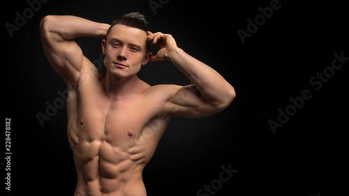 Przystojny szczupły mężczyzna z mięśniowym ciałem. Zbliżenie dysponowany młodego człowieka podbrzusze przeciw ciemnemu tłu.