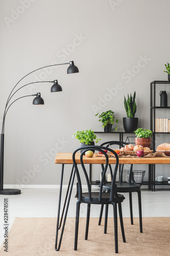 Sticker Lamp and plants in grey dining room interior with black chairs at wooden table with food. Real photo