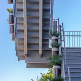 White stairs with potted plants against clear sky - 228479934
