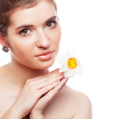 A beautiful woman with narcissus flower in her hand. Portrait of young girl with clean and healthy skin. Isolated on a white background