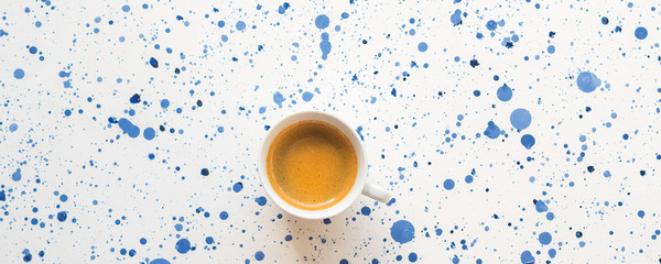Cup of espresso coffee on white and blue dots abstract background. Morning breakfast coffee break concept flat lay © tenkende