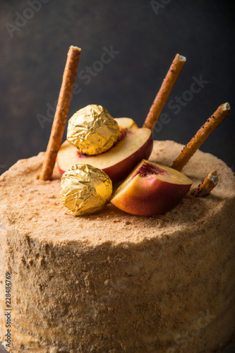 Sticker festive cake decorated with golden candies and peach