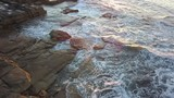 View of water flowing in a stack of rocks on the coastline. - 228488170