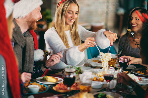 Friends having dinner at home at Christmas eve. Winter holidays concept. - 228489150