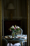 Elegant romantic table set for two in hotel room, champagne, fruit, cheese, crackers and flowers. - 228497354