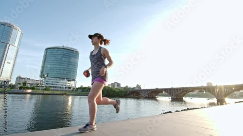 Poster Tracking of muscly female runner jogging along embankment on sunny summer day; buildings in background