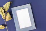 A blue wooden frame and a dried leaf. Watercolor paper inside the frame with place for text. Blue-purple background made of pastel embossed paper. Top View. The composition is cropped at an angle. - 228499379