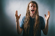 Young man screaming on a solid background