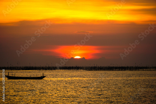 Small fishing boat with sunset light