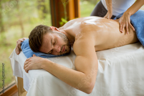 Leinwanddruck Bild Young man having massage in the spa