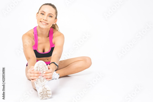 Sticker Fit woman stretching her leg to warm up - isolated over white background