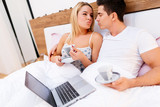 Couple in love holding coffee while in bed - 228536719